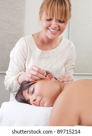 Acupuncturist placing needle in ear in auricular acupuncture treatment