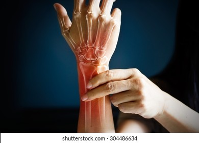Acute pain in a woman wrist, colored in red on dark blue background, Health issues problems