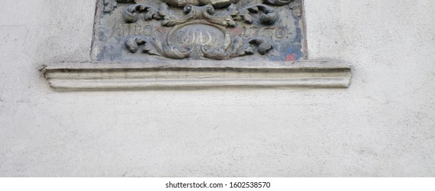 "AD 1770 (""Anno [Domini] 1770"") carved into a stone plate placed above the entrance to a building erected that year (carrying also the initials I A S). Originally painted"