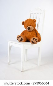 ad old teddy bear sits on a white wooden chair