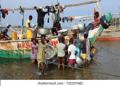 ADA FOAH - GHANA - AUGUST 11, 2017: Unidentified women buy fish on August 11, 2017 in Ada Foah, Ghana. Illegal fishing by foreign vessels threatens the traditional fishing villages in Ghana.