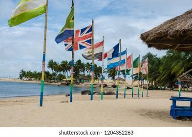 Ada Foah, Volta River delta, Ghana - September the 13th 2018. Flags on the lagoon beach.