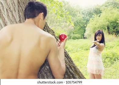 Adam holds out an apple to Eve