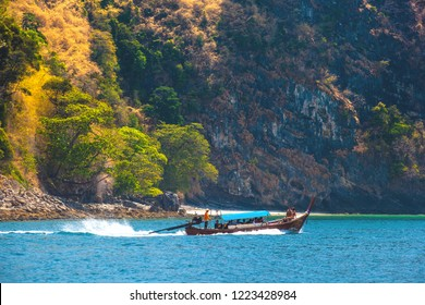 Adaman Sea, AO Nang, Krabi, Thailand - Februrary 2014. Longtail transport boat carries passengers to tropical islands in the clear sunny day, trees sticking out of the rocks on the coast.