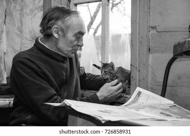ADAMIVKA, UKRAINE - 26 January 2009: A man playing with kittens and reading a newspaper in a country house