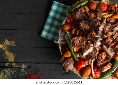 Adana, Lamb and Chicken Kebab serving with stuffed meatballs, lahmacun, salad, yogurt, onion, pepper, bulgur and parsley on rustic black wood table. Dark photography concept with copy space. Top view.