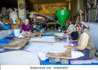 "Adana, Turkey 27 June 2019. Traditional turkish  bread. Also known as ""yufka ekmek"" ,  natural organic homemade yufka bread. Woman rolls out dough, close-up. Making Turkish traditional bread"