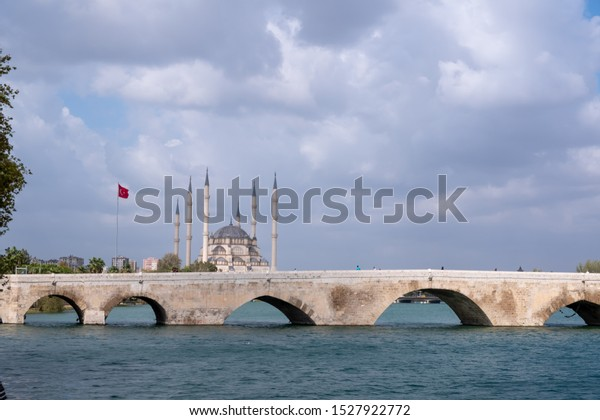 Adana, Turkey - October, 2019: Adana Central Mosque. Adana Sabanci Central Mosque, Turkey. Sunny day and a blue clouds sky. Adana historic stone bridge