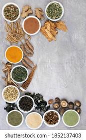 Adaptogen gesunde Lebensmittel mit Kräutern, Gewürzen und Zusatzpulver. Pflanzliche Lebensmittel, die dem Körper helfen, Stress zu bewältigen und normale physiologische Funktionen zu fördern oder wiederherzustellen. Draufsicht auf grauem Hintergrund