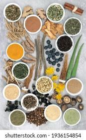 Adaptogen gesunde Lebensmittel mit Kräuter, Gewürzen und ergänzen Pulver. Natürliche pflanzliche Lebensmittel, die dem Körper helfen, Stress zu bewältigen und normale physiologische Funktionen zu fördern oder wiederherzustellen. Auf hellgrauem Hintergrund.