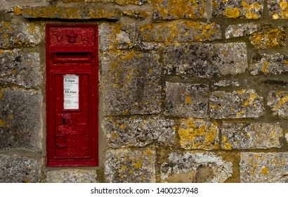 Adber, Dorset. England- April 29, 2019: A 19th Century, Victorian wall mounted red postal box with VR cypher, set in a weathered local stone wall, covered in lichen. In use daily on public street.