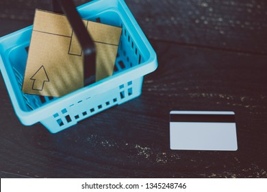 add to cart concept: cardboard online delivery parcel in shopping basket and payment card next to it