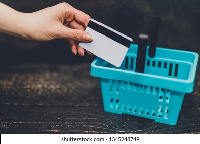 add to cart concept: hand holding payment card with shopping basket next to it