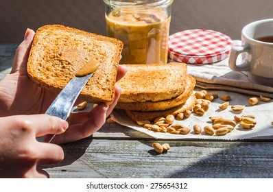 add to ruddy toast peanut butter, hand, delicious breakfast on a gray background