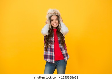 Add some personality to cold weather wardrobe. Happy child wear faux fur hat. Little girl smile in hat yellow background. Fluffy and warm trapper hat for kid. Fashion hat for outdoor adventures.