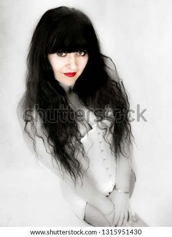 Added grain and blur for creative effect. Attractive sexy woman, colourpop portrait. High angle view, making eye contact. Long black hair and red lips.