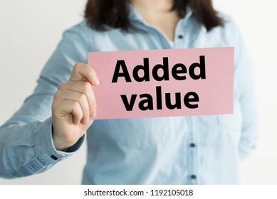 Added Value message on a pink card hold by a woman, business concept image with soft focus background