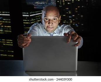 addict businessman alone at night sitting at office computer laptop watching porn or online gambling isolated on black background on internet chat addiction concept