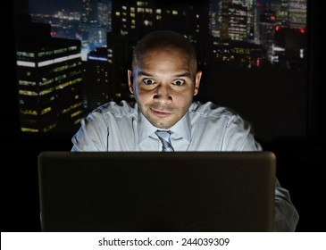addict businessman alone at night sitting at office computer laptop watching porn, online gambling or working late in addiction concept