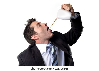addict businessman in suit and tie drinking cup of coffee pouring stream on his mouth anxious and crazy in caffeine addiction and need to keep awake isolated on white background