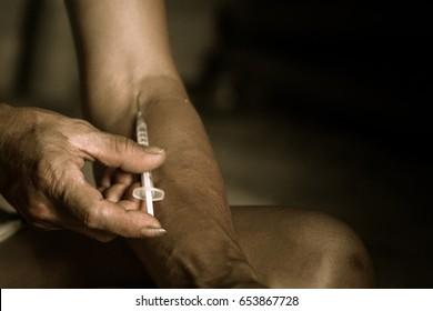 Addict lady with syringe using drugs.