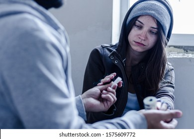 Addict young woman have meeting with  dealer in abandoned building, to buy dose of white powder cocaine. Teenage homeless girl is going to take coke, amphetamines. Drug addiction concept.