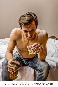 Addicted and depressed men sitting in bedroom with glass of alcohol in hand.