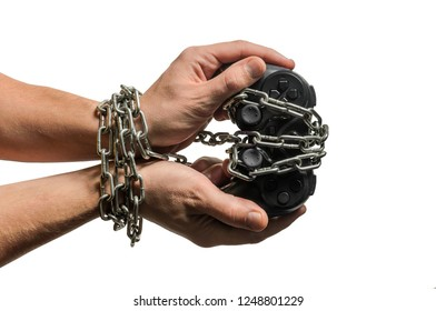 Addicted gaming player's hands with joystick chained in chains isolated on white background