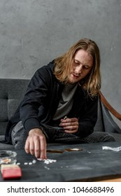 addicted junkie taking mdma pill from table