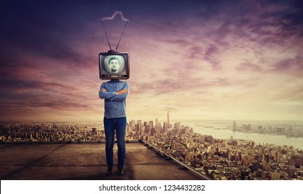 Addicted man with crossed arms and old tv instead of head standing on skyscraper rooftop over big city sunset horizon. Television manipulation and brainwashing concept. Mass media propaganda control.