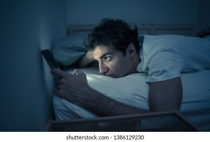 Addicted to social media young man chatting and surfing on the Internet on smart phone at night in bed. Sleepless in dark bedroom with mobile screen light. In insomnia and online network addiction.