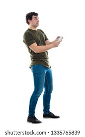 Addicted young man playing video games isolated over white background. Excited guy stand all ears holding a joystick console looking attentive try to win, having fun in the virtual world.