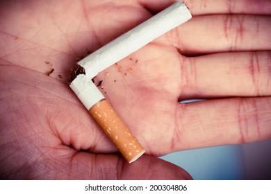 Addiction. Closeup of the broken cigarette on female hand. Quit smoking. Studio shot.
