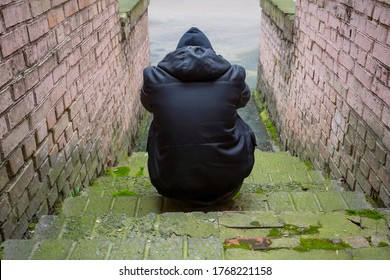 Addiction concept. A drug addict in a hood sits in an abandoned house after taking drugs. Fighting addiction, view from the back.