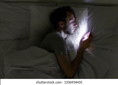 Addiction, nomophobia, insomnia, sleep disorder concept. Male addicted to the smartphone connected 24/7 to internet, lying on bed and using smart phone at late night.