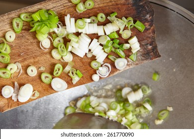 Adding cut leek to the cooking on the wok