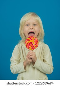 Adding excitement to snack time. Happy candy girl. Small girl hold lollipop on stick. Small child with sweet lollipop. Happy childhood food.
