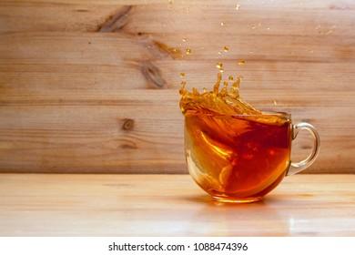 Adding lemon to tea in transparent cup