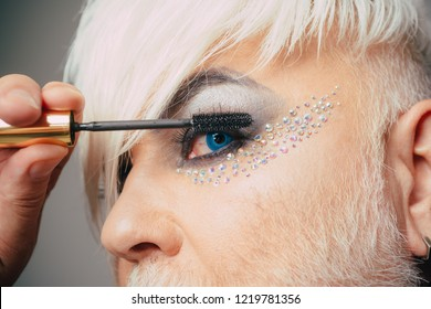 Adding length and volume. Fashion male eye makeup. Transgender man apply mascara. Transgender man wear eyeshadows and eyebrow makeup. Male makeup look. Male makeup artist.