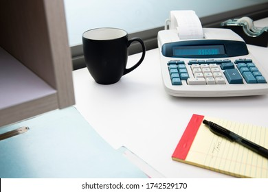 Adding machine with coffee cup, notepad, and filefolder on office desk