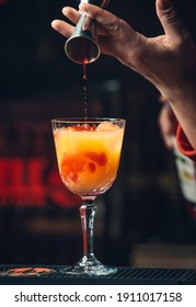 adding red syrup into orange cocktail