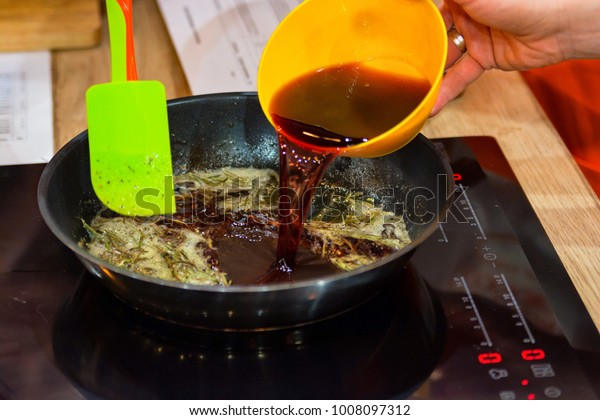 Adding red wine to food on frying pan