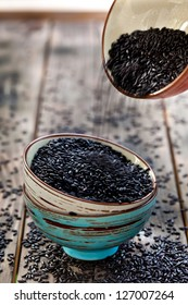 Adding rice to the stack of bowls with black raw rice