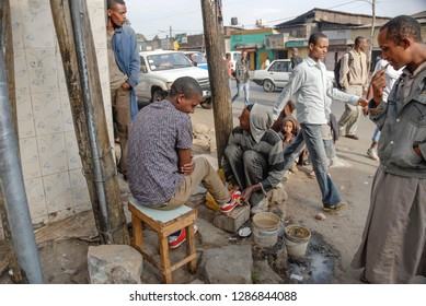 ADDIS ABABA, ETHIOPIA - MARCH 30 2012: Unidentified shoe shiner cleans shoes of his client at Mercato in Addis Ababa, Ethiopia. Shoeshine is a common way to start doing small business in Addis Ababa.