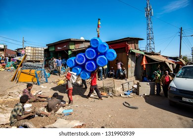 Addis Ababa/Ethiopia -02.16.2019: Men carring plastc barrels on the city market