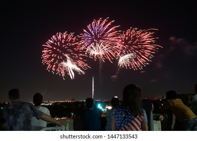 """Addison, TX / USA - 7/3/2019: Spectators look out a fireworks show from a rooftop parking garage. The celebration is part of """"Kaboom Town"""" an annual event hosted by the city of Addison for July 4th."""