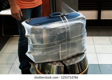 Additional packing of baggage at the airport before the trip, the worker wraps the suitcase with a transparent film