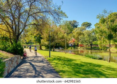 Adelaide, Australia - April 14, 2017: Unrecognized people riding their bicycles along Torrens river bike track in North Adelaide on a bright day