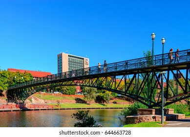 Adelaide, Australia - April 14, 2017: Unrecognised people walking across University Bridge through Torrens river in North Adelaide on a bright day