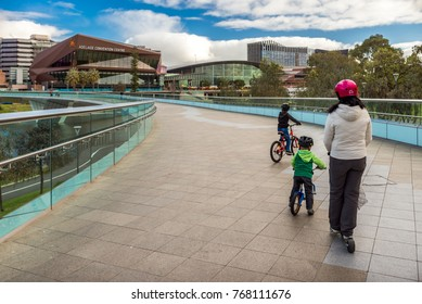 Adelaide, Australia - August 27, 2017: Mother with two sons ridind bicycles along Torrens footbridge in Adelaide city on a day